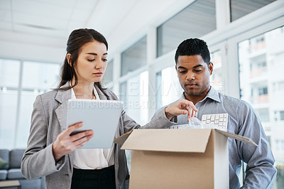 Buy stock photo Shot of a young businessman and businesswoman unpacking a box of computer equipment in a modern office