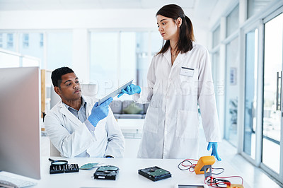 Buy stock photo Shot of a young man and woman repairing computer hardware in a laboratory