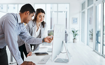 Buy stock photo Shot of a young businessman and businesswoman using a computer in a modern office