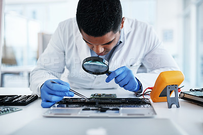 Buy stock photo Shot of a young man using tweezers and a magnifying glass while repairing computer hardware in a laboratory