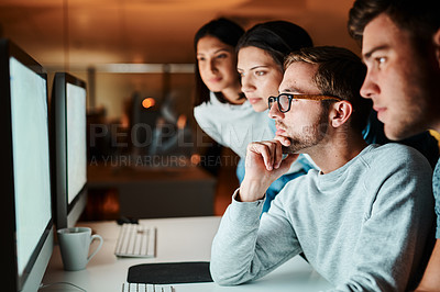 Buy stock photo Shot of a of colleagues looking at a computer screen while working late