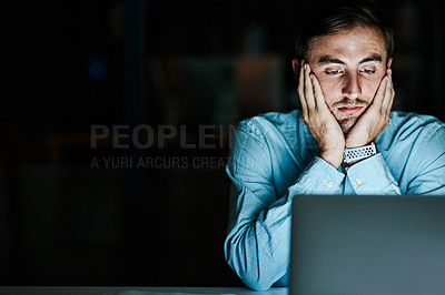 Buy stock photo Shot of a young businessman looking stressed while using his laptop in an office at night