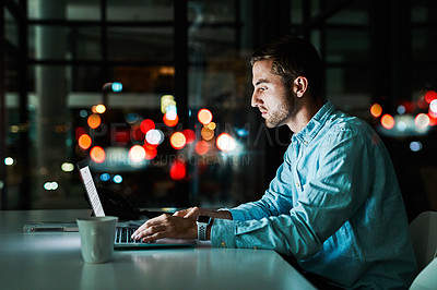 Buy stock photo Shot of a businessman working on a laptop in an office at night