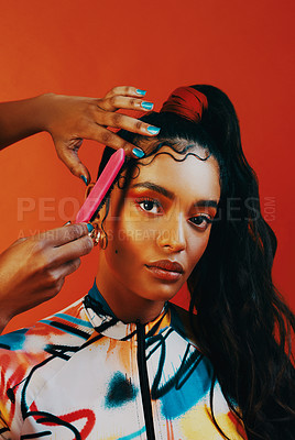Buy stock photo Studio shot of a hairstylist doing a woman's edges against a orange background