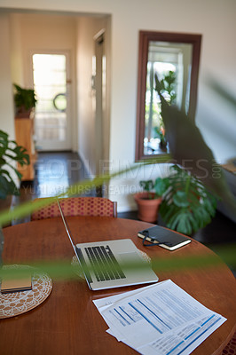 Buy stock photo Shot of a laptop and other various business items on a table in the living room at home