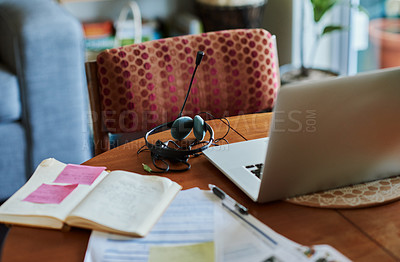 Buy stock photo Shot of a laptop and headset on a table in the living room at home