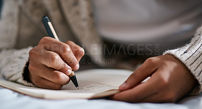 Buy stock photo Cropped shot of a man writing in a notebook on his bed at home
