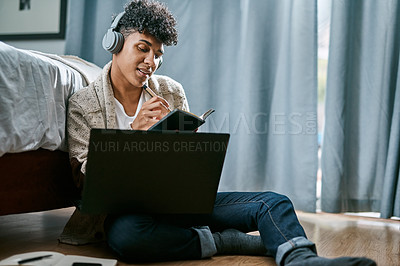 Buy stock photo Shot of a young man writing in a notebook and using a laptop while listening to music at home