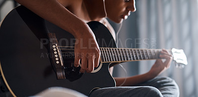 Buy stock photo Cropped shot of a young man playing the guitar in his bedroom at home