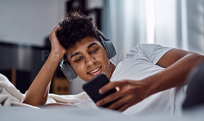 Buy stock photo Shot of a young man using a smartphone and headphones while relaxing on his bed at home