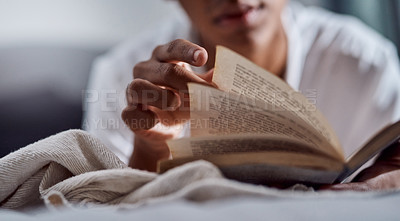 Buy stock photo Cropped shot of a young man reading a book and relaxing on his bed at home