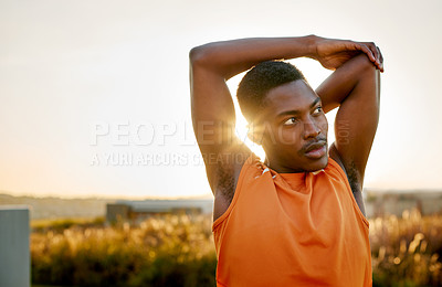 Buy stock photo Shot of a sporty young man stretching his arms while exercising outdoors
