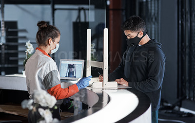 Buy stock photo Shot of a young man filling in paperwork at the reception desk of a gym