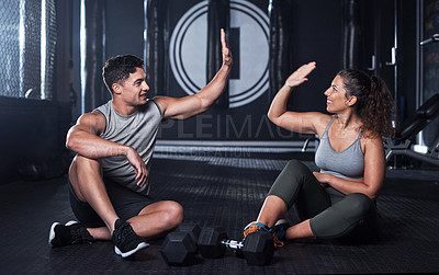 Buy stock photo Shot of two sporty young people giving each other a high five while exercising together in a gym