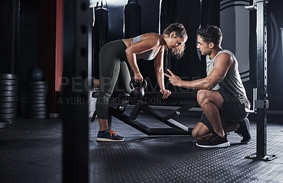 Buy stock photo Shot of a sporty young woman exercising with a fitness instructor in a gym