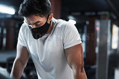 Buy stock photo Cropped shot of a handsome and athletic young man wearing a mask while working out in the gym