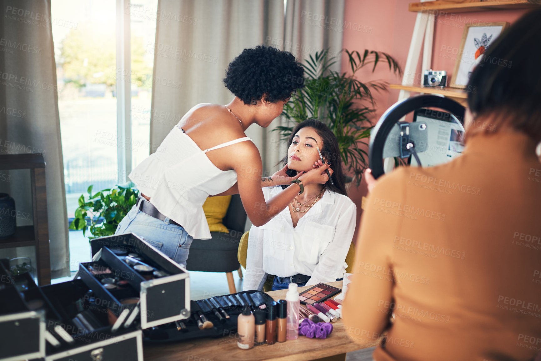 Buy stock photo Shot of a woman getting her makeup done while being recorded