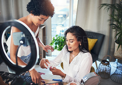 Buy stock photo Shot of two women doing a makeup tutorial for their blog