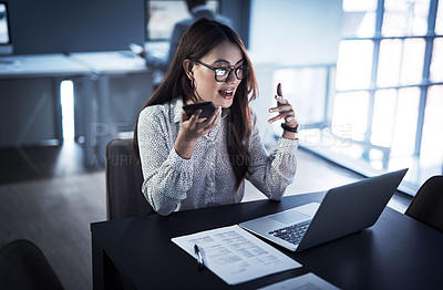 Buy stock photo Shot of a young businesswoman using a cellphone and laptop while working in an office at night