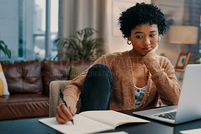 Buy stock photo Shot of a young woman writing notes while working on a laptop at home