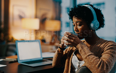 Buy stock photo Shot of a young woman drinking coffee while working from home at night
