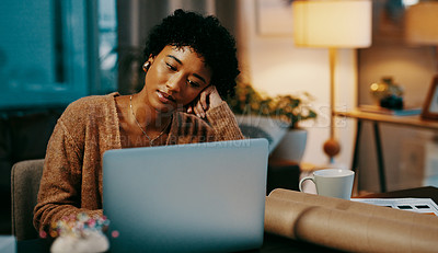 Buy stock photo Shot of a young woman looking bored while working on a laptop at home