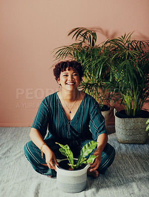Buy stock photo Shot of a beautiful young woman sitting on the floor with a houseplant