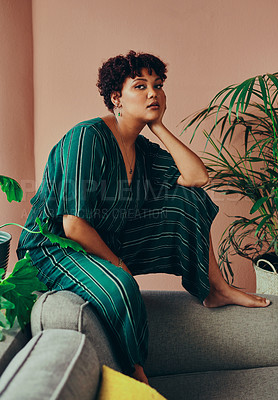 Buy stock photo Shot of a beautiful young woman sitting on the couch at home