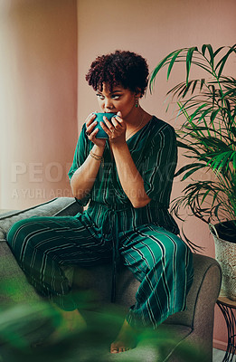 Buy stock photo Shot of a beautiful young woman drinking coffee while sitting on the couch at home