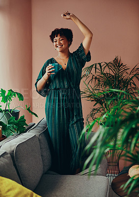 Buy stock photo Shot of a beautiful young woman holding a cup of coffee while standing on the couch at home