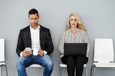 Buy stock photo Studio shot of a businessman and businesswoman using their wireless devices while waiting in line against a grey background