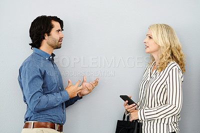 Buy stock photo Studio shot of a businessman and businesswoman having a discussion against a grey background