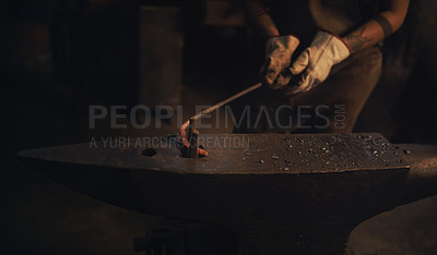 Buy stock photo Shot of a blacksmith working with a hot metal rod in a foundry