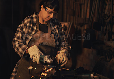 Buy stock photo Shot of a young woman using an angle grinder while working at a foundry