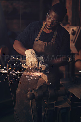 Buy stock photo Shot of a young man using an angle grinder while working at a foundry
