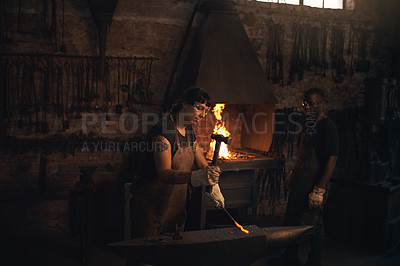 Buy stock photo Shot of a young woman hitting a hot metal rod with a hammer in a foundry