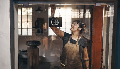 Buy stock photo Shot of a young woman hanging an open sign at the entrance of a foundry