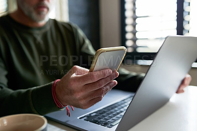 Buy stock photo Cropped shot of an unrecognizable man sitting at home with his laptop and cellphone