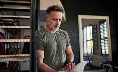 Buy stock photo Cropped shot of a mature man reading a book at home