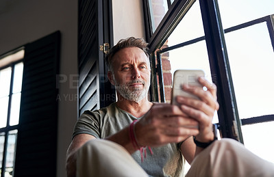 Buy stock photo Cropped shot of a man using his cellphone while sitting at home