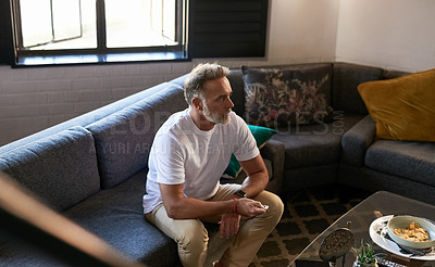 Buy stock photo Shot of a man using a remote control while sitting at home