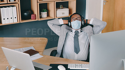 Buy stock photo Shot of a businessman wearing a mask while listening to music through headphones at his desk