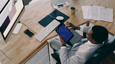 Buy stock photo Shot of a businessman wearing headphones while using a digital tablet at his desk