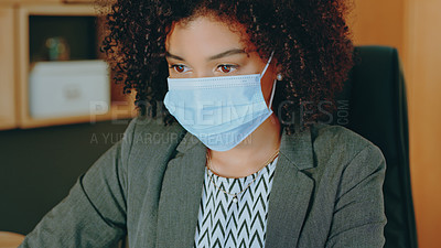 Buy stock photo Shot of a young businesswoman wearing a mask while working in a office