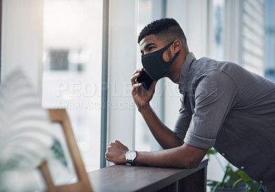 Buy stock photo Shot of a young businessman wearing a face mask while talking on a cellphone in an office