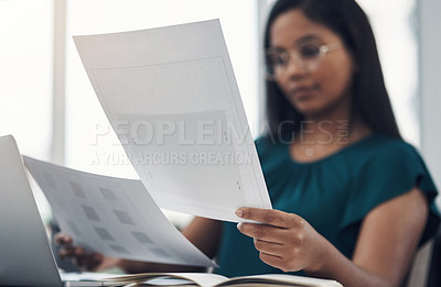 Buy stock photo Closeup shot of a young businesswoman going through paperwork in an office