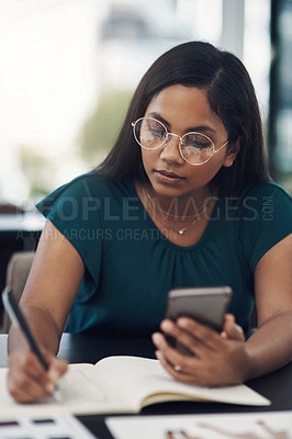 Buy stock photo Shot of a young businesswoman writing notes while using a cellphone in an office