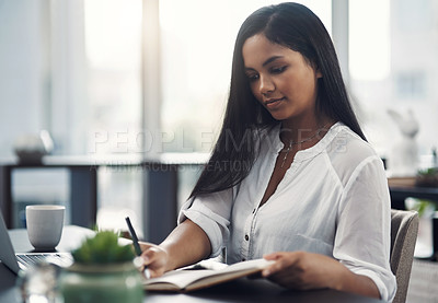 Buy stock photo Shot of a young businesswoman writing notes while working on a laptop in an office
