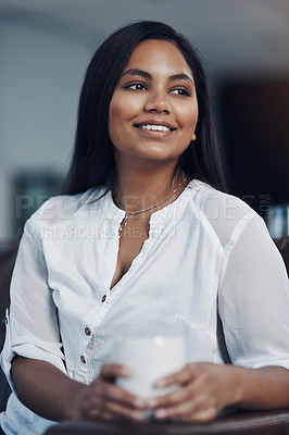 Buy stock photo Shot of a young businesswoman drinking coffee while taking a break in an office
