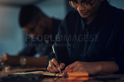 Buy stock photo Shot of a young technician writing in a notebook while repairing computer hardware